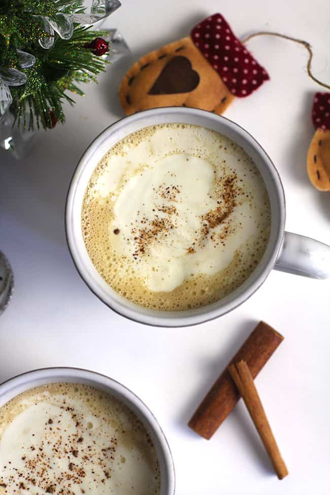 Overhead shot of a mug of homemade eggnog latte, with cream on top.