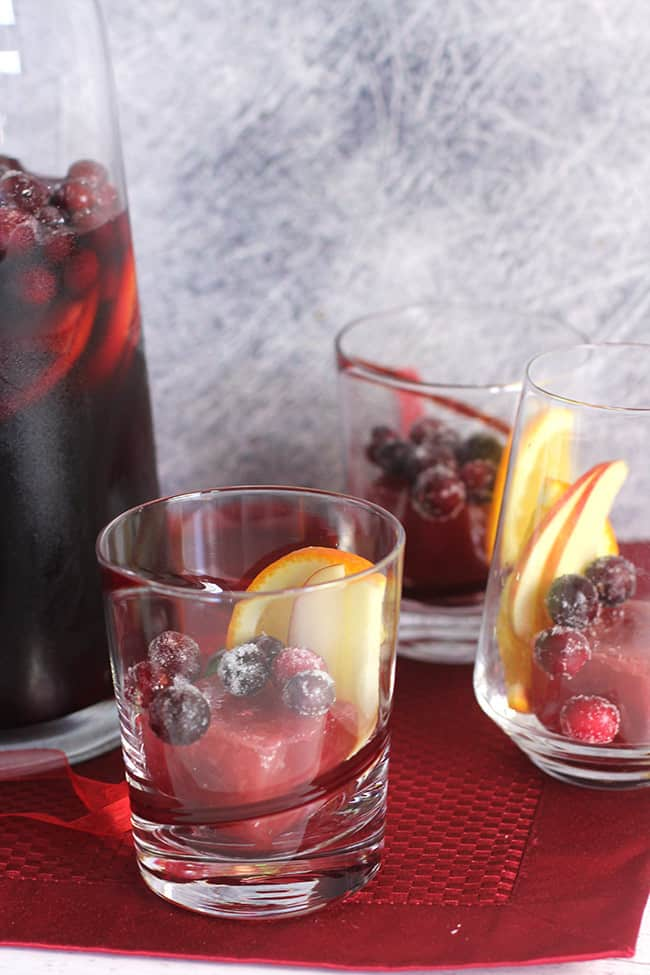 A pitcher of sangria with some glasses filled with flavored ice cubes and garnish.