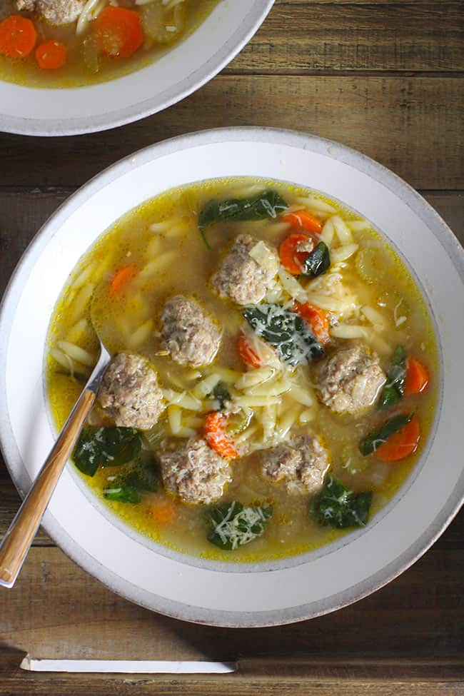 Overhead shot of two bowls of Easy Italian Wedding Soup on a wooden tray.