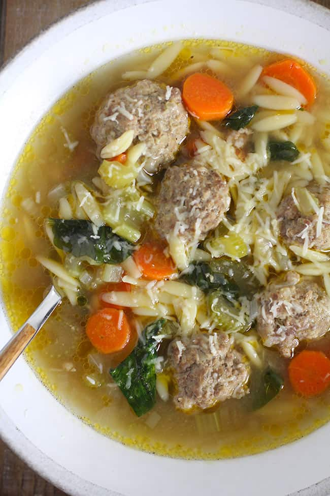 Close up of a white bowl of Italian Wedding Soup, with parmesan cheese.