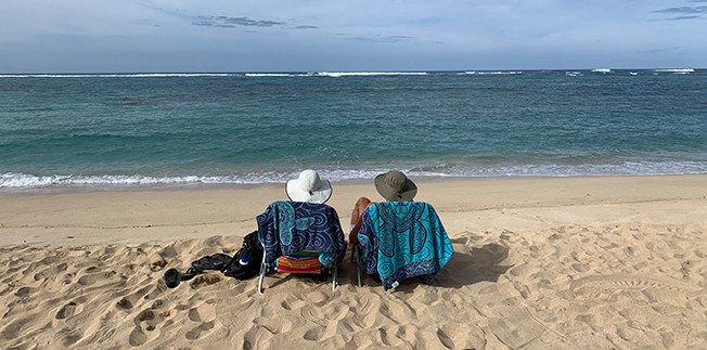 A picture of Mike and I sitting on beach chairs in Oahu, staring at the ocean.