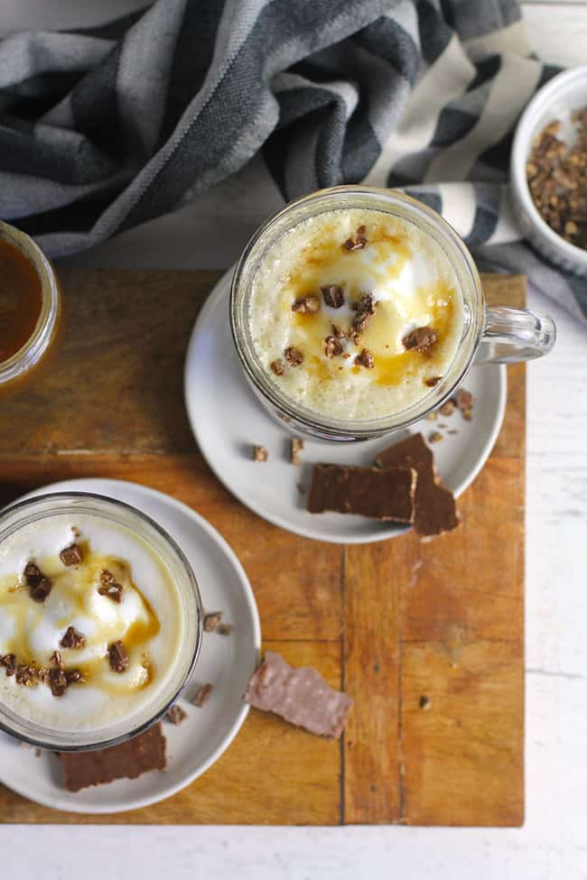 Two mugs of homemade caramel lattes, with chocolate toffee candies on top.
