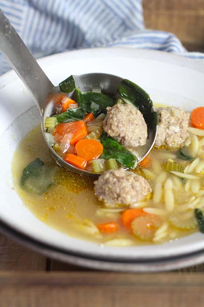 A soup ladle filling a serving bowl of soup.