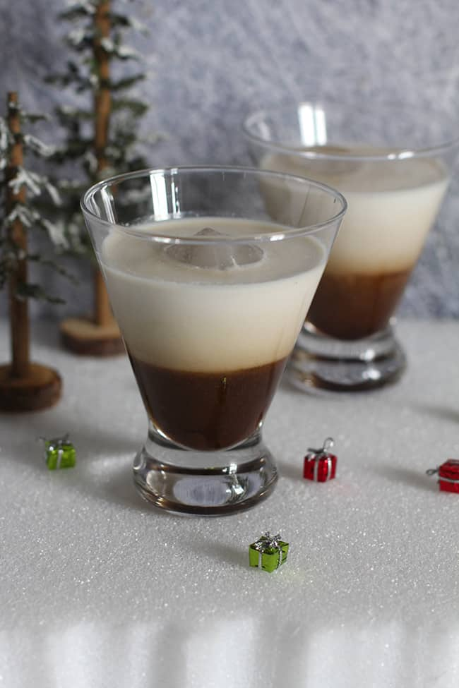 Side shot of two glasses of White Russian cocktails, on a white surface.