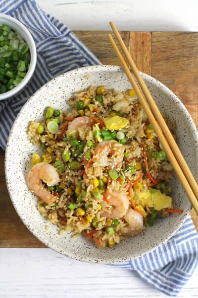 Overhead shot of a bowl of shrimp fried rice, with some chopsticks, on a wooden board.