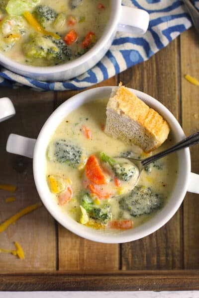 Overhead view of two white bowls of creamy broccoli cheddar soup, with toasty bread on a wooden tray.