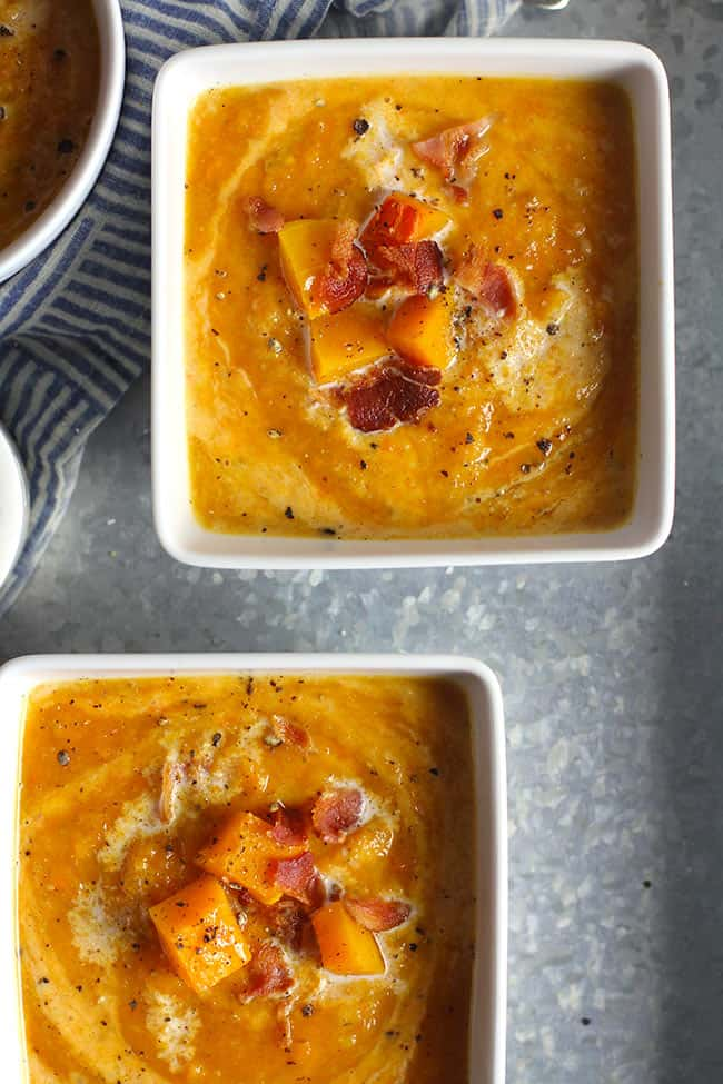 Two square white bowls of butternut squash soup with bacon.