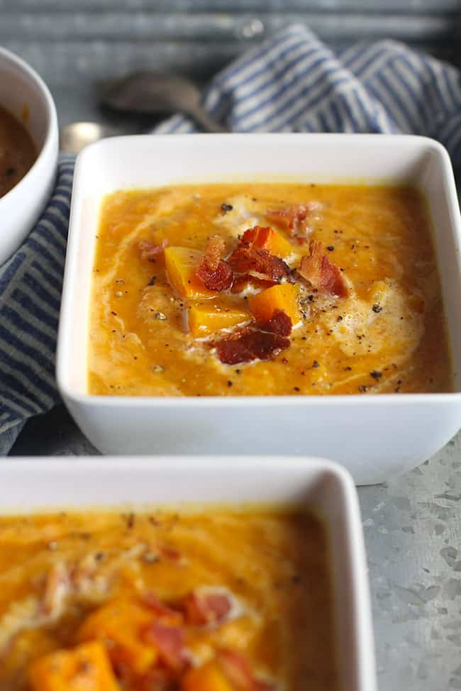 Side shot of two square bowls of butternut squash soup with bacon.