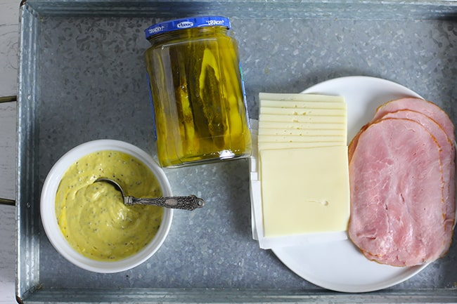 A gray tray with the other Cuban sandwich ingredients - aioli, pickles, ham, and Swiss.