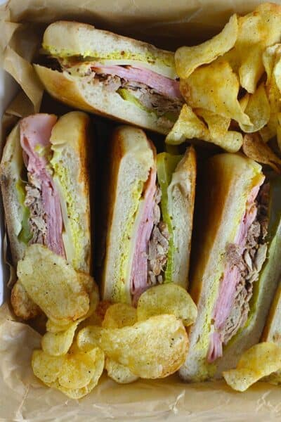 A square dish with four pressed cuban sandwiches, showing the insides of the sandwiches.