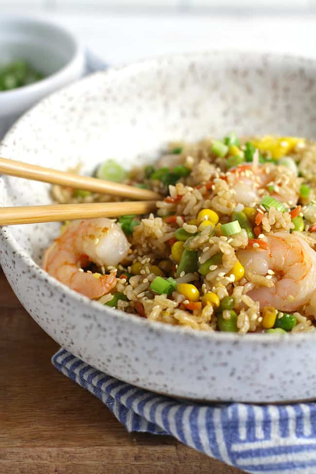 Side shot of a speckled bowl of shrimp fried rice, with chopsticks.