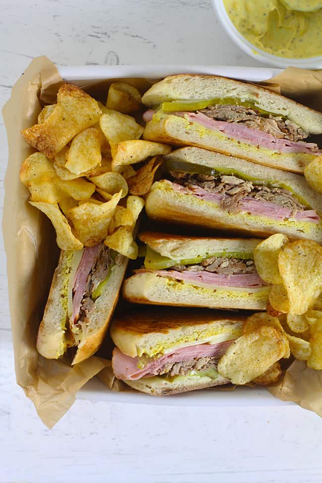 A square dish of cuban sandwiches plus chips.