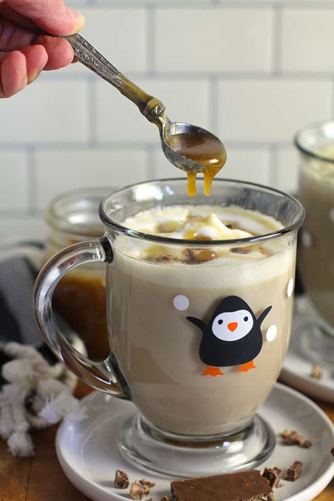 A clear penguin mug full of caramel latte, and a spoon dripping extra caramel on top.