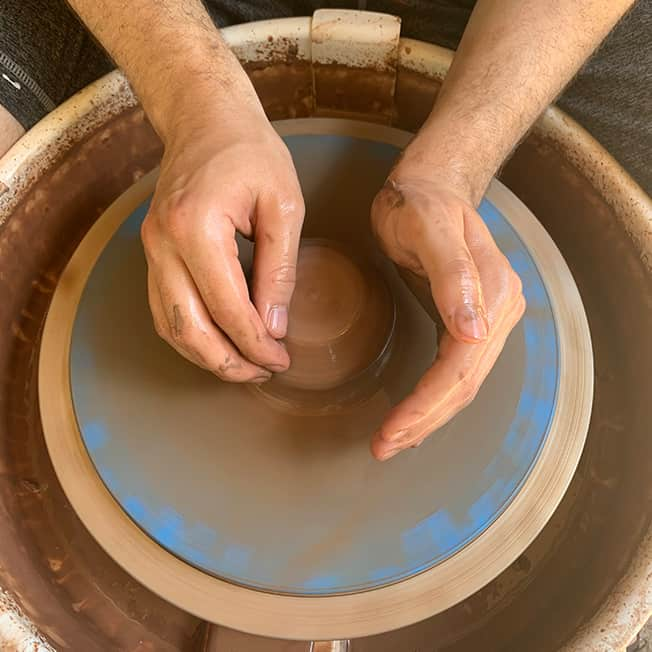 A picture of Zach's hands on the pottery wheel.