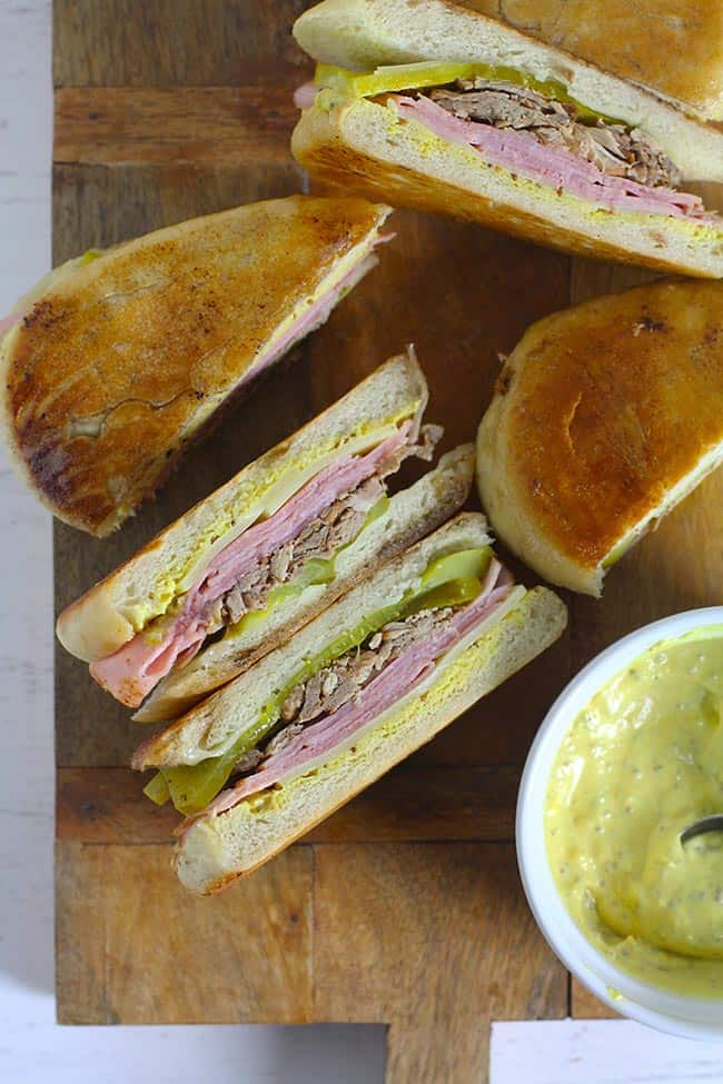 Sliced cuban sandwiches on a wooden board with mustard aioli sauce.