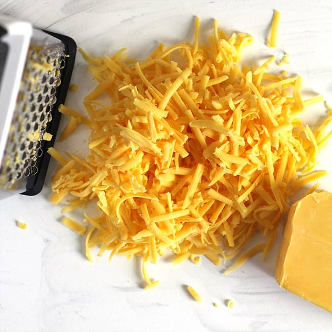 Overhead view of some shredded cheddar cheese with a box grater.