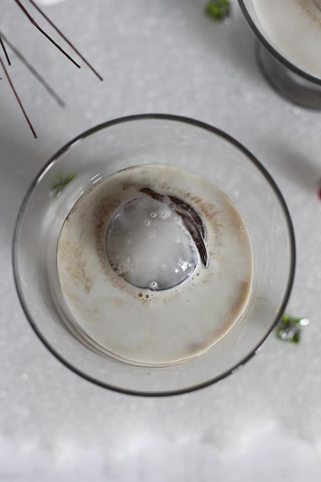 Overhead shot of a creamy White Russian cocktail with a round ice cube.