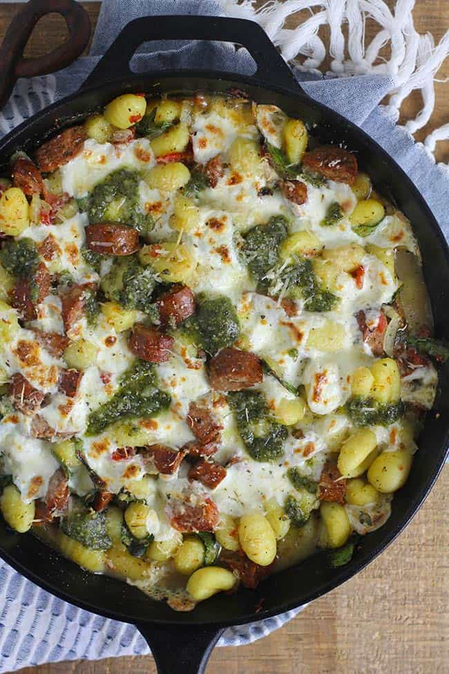 Overhead shot of a large cast iron skillet with sausage and gnocchi.