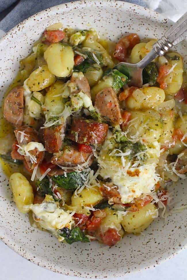 Closeup of a serving of sausage and gnocchi with a fork.