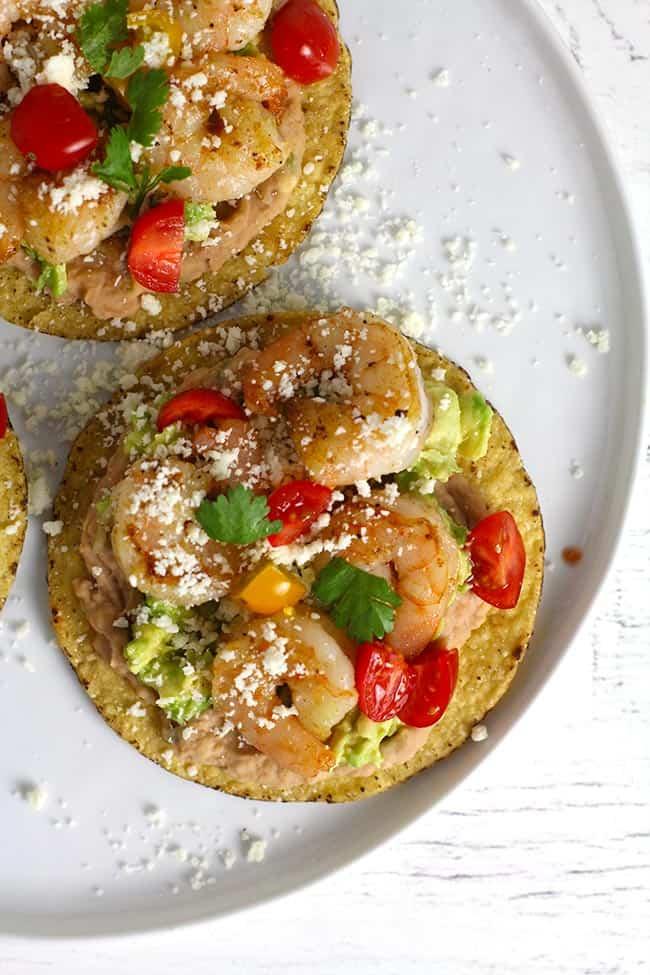 A close up on one shrimp tostada with refried beans and avocado.