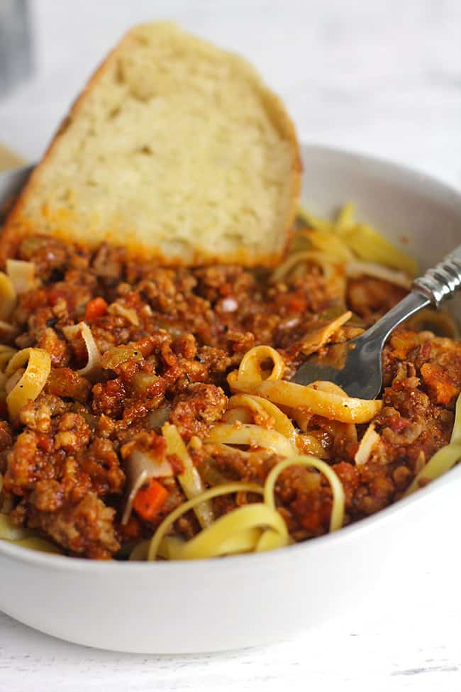 Side shot of pasta and bolognese sauce, with a piece of bread.