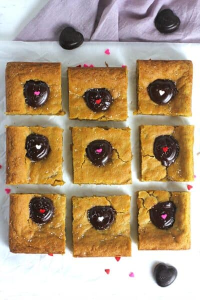 Overhead shot of nine sliced brown butter blondies, with chocolate hearts.