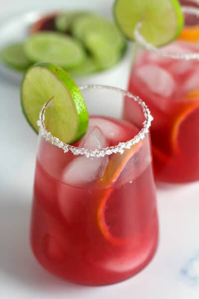 Two glasses of blood orange margaritas with salty rims.