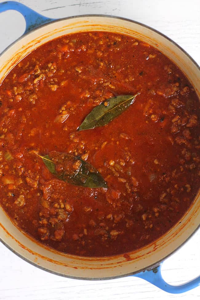 Overhead view of a stock pot of bolognese sauce, with bay leaves.