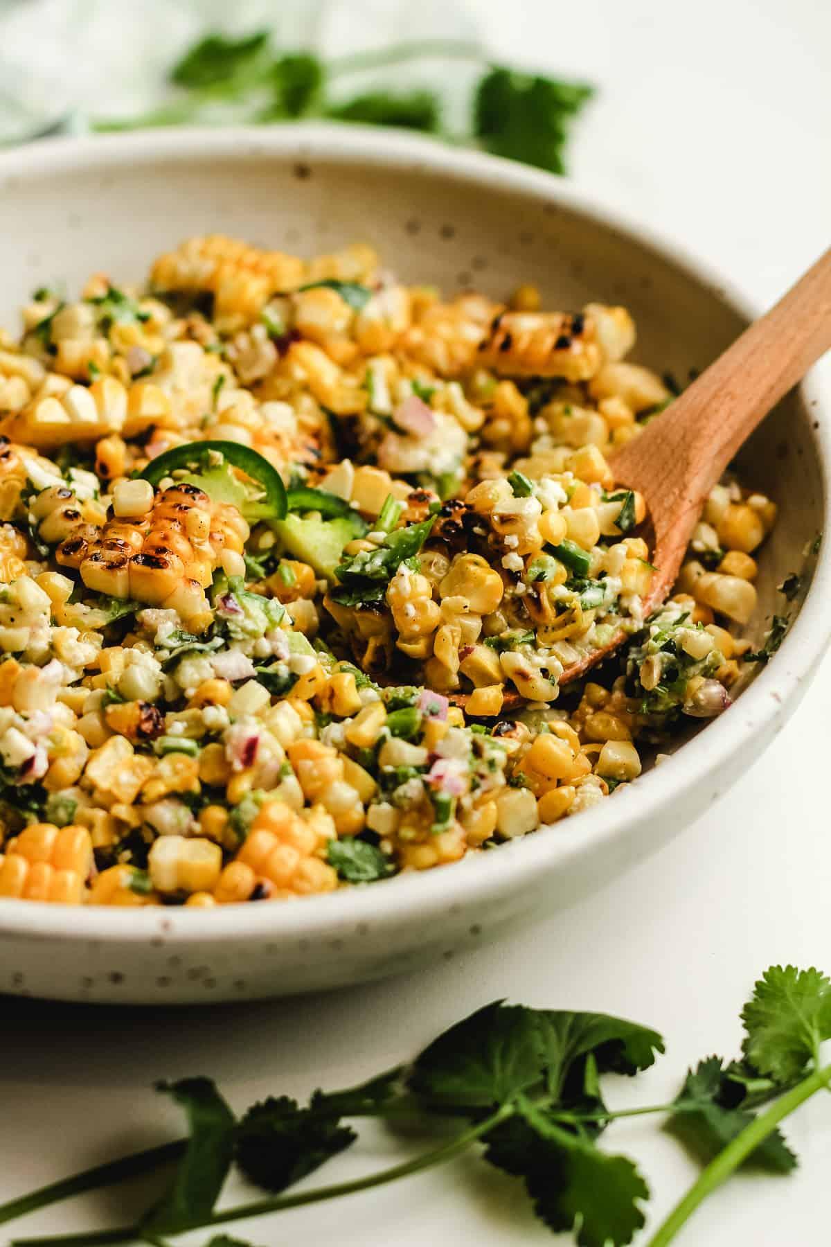 Side shot of a bowl of street corn salad.