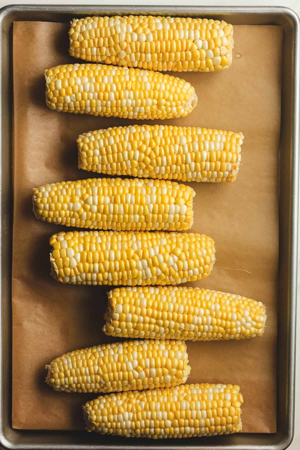8 medium ears of corn on a baking sheet.