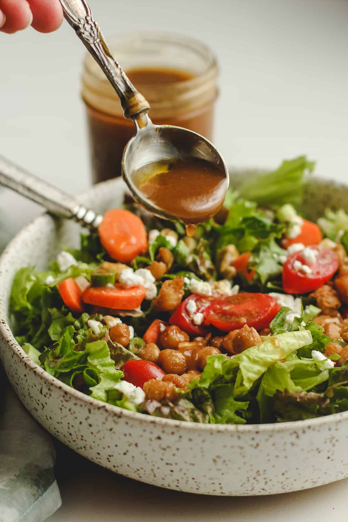 A hand drizzling some balsamic dressing on a green salad.