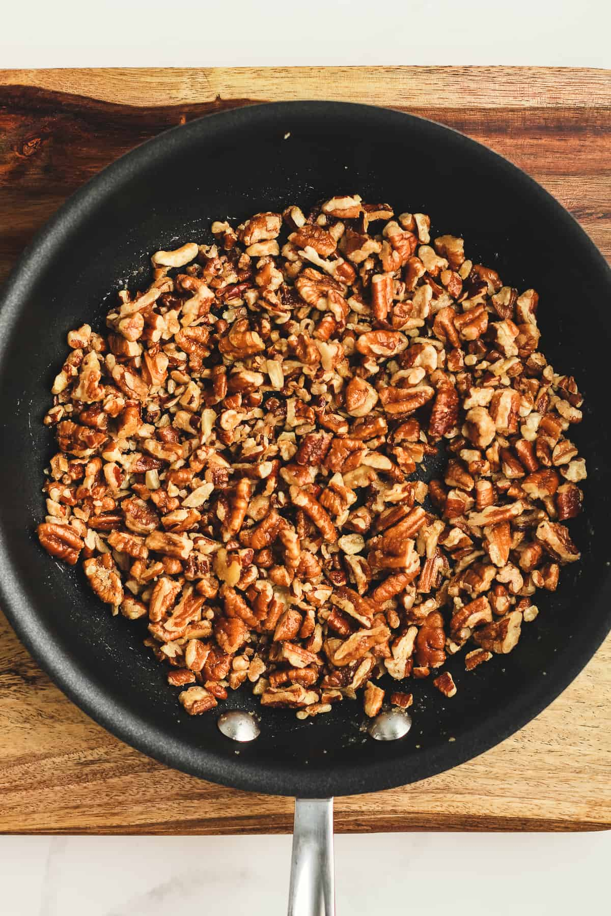 A skillet of chopped pecans.