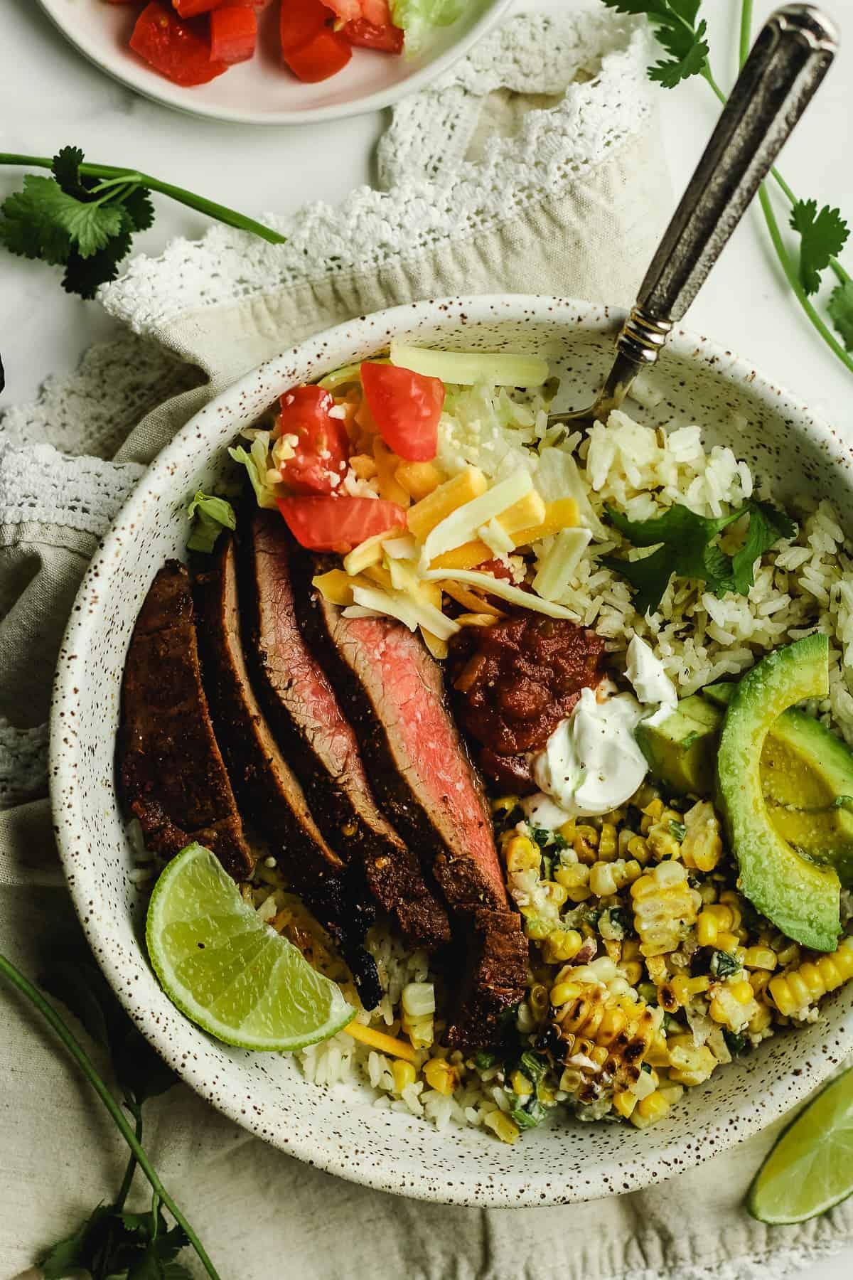 Closeup shot of carne asada burrito bowls with Mexican Street Corn.