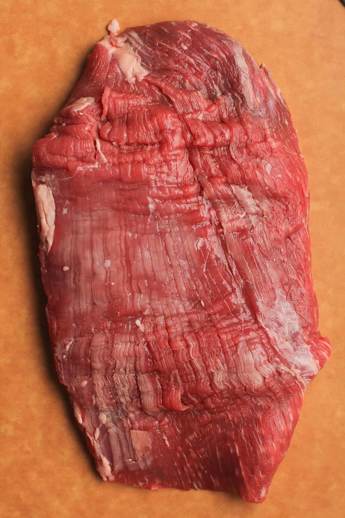 A raw flank steak on a cutting board.