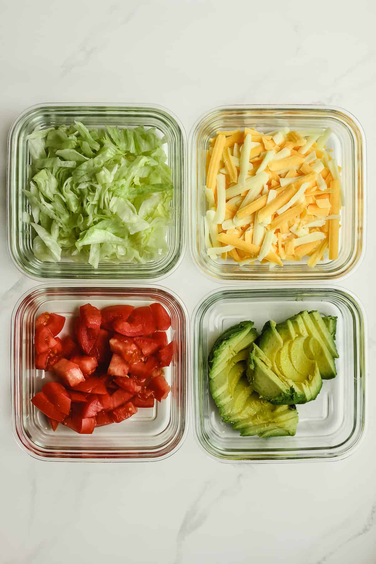 Four square glass bowls of condiments - lettuce, cheese, tomato, and avocado.
