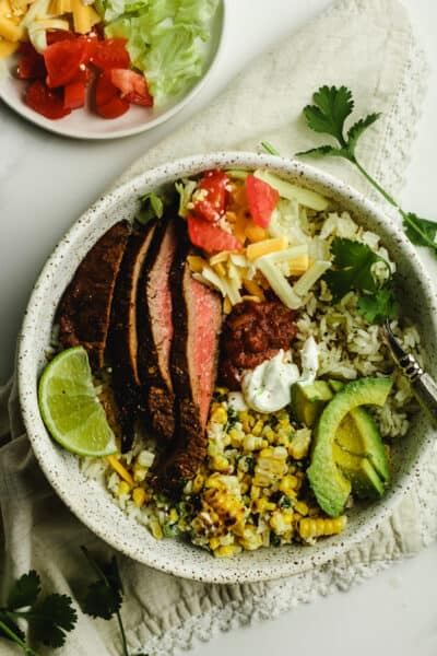 A bowl of carne asada burrito bowl with a fork.
