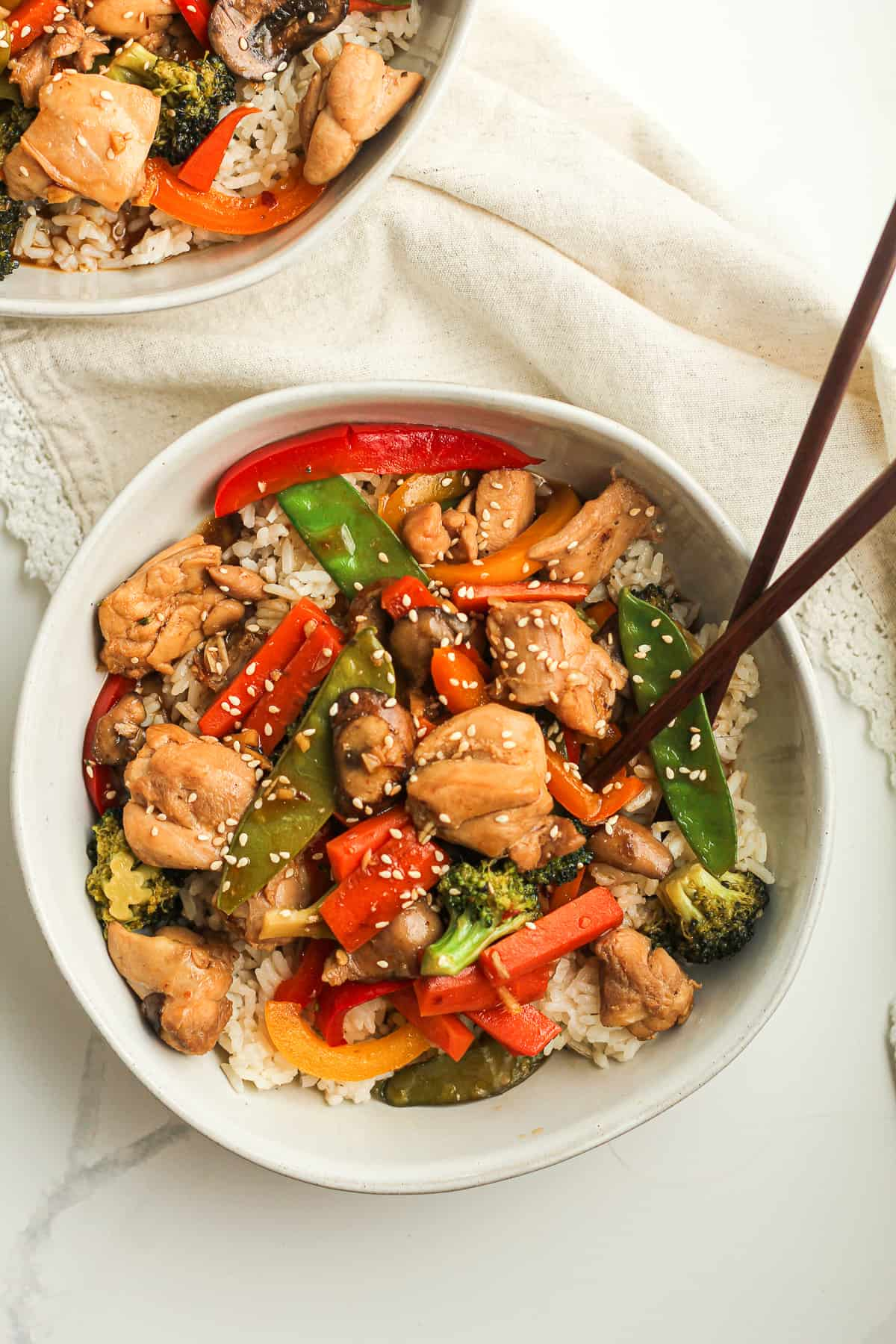 Two bowls of chicken vegetable stir fry.