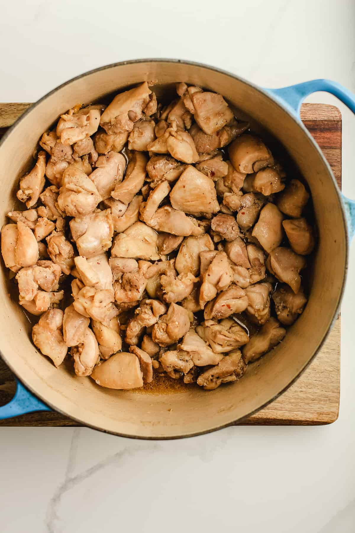 A stock pot of cooked chicken thighs in bite-sized pieces.