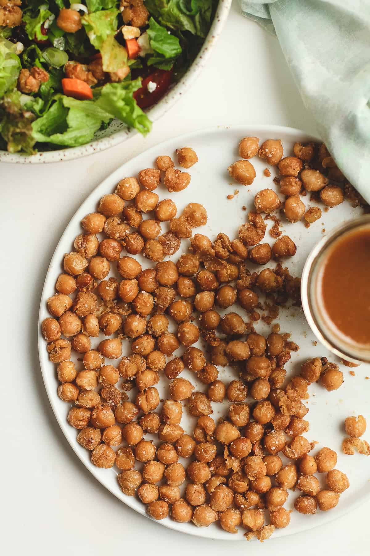 A plate of crispy chickpeas with dressing, next to a green salad.