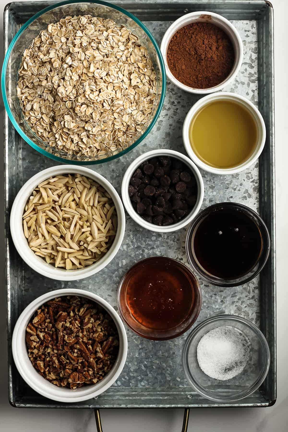 A gray tray of ingredients for chocolate granola.