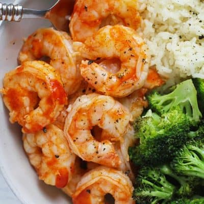 Close up shot of a white bowl of honey sriracha shrimp with rice and broccoli.