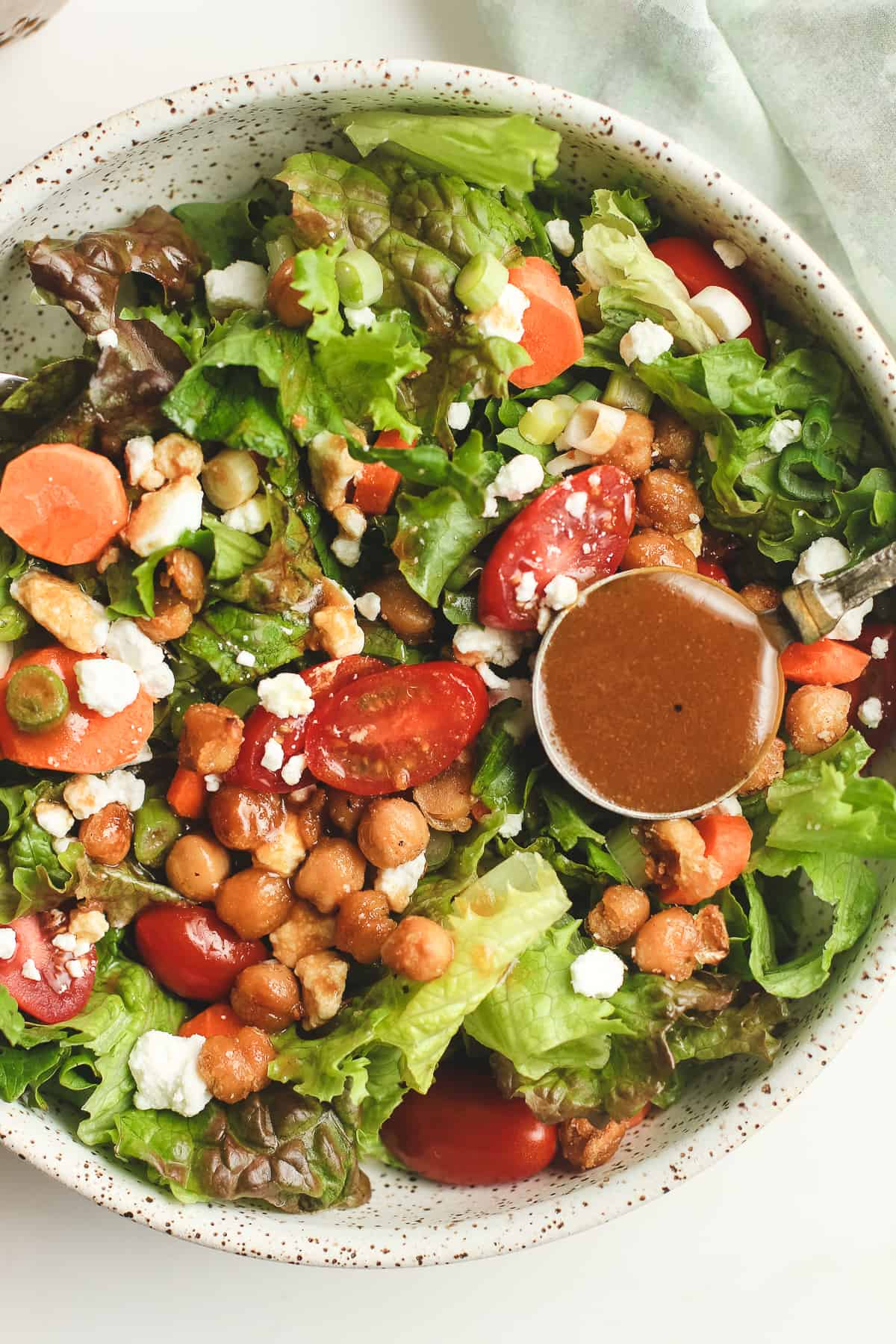 A green salad with some crispy chickpeas and some balsamic vinaigrette.