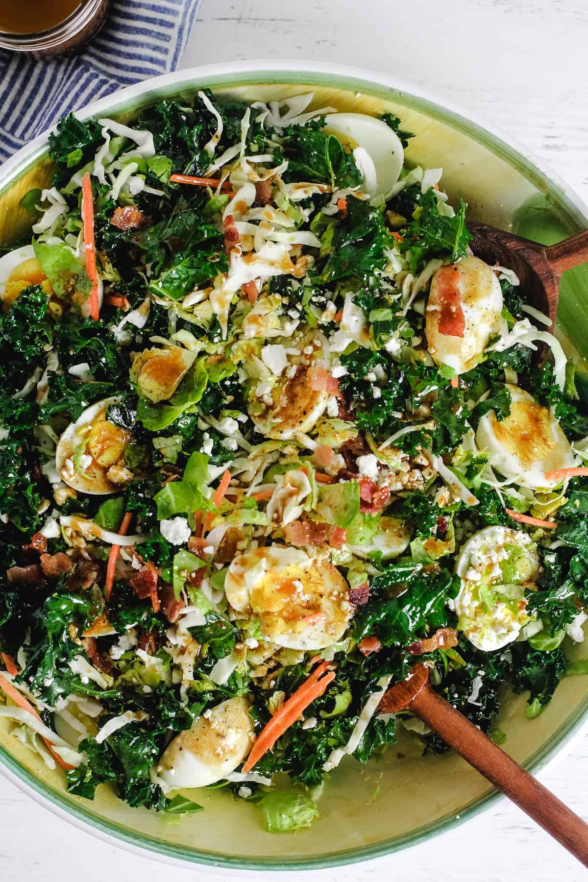 A large bowl of cruciferous salad with salad tongs.