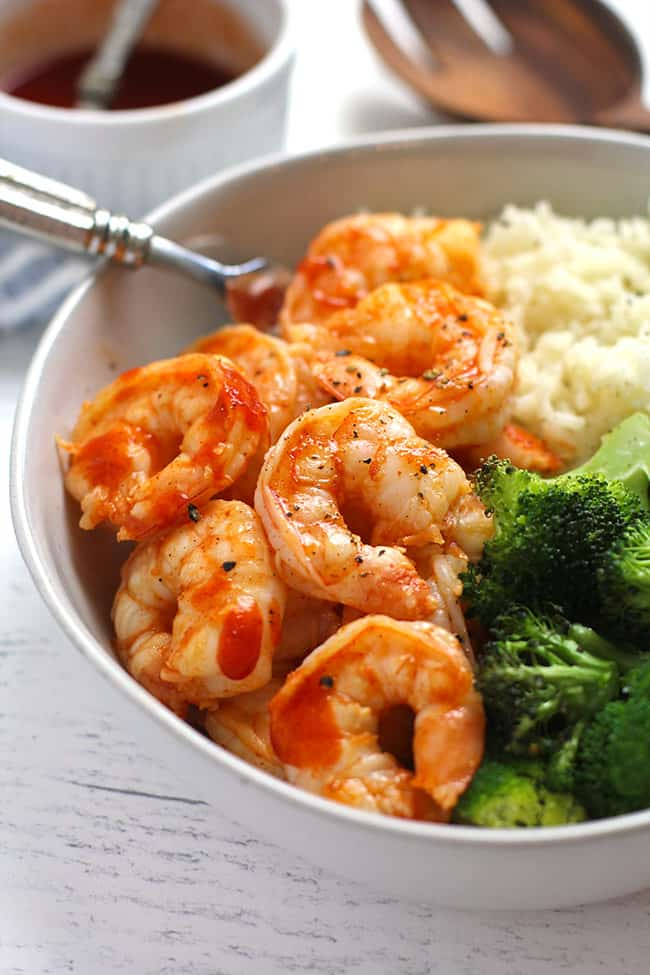 Side shot of a honey sriracha shrimp bowl, with rice and broccoli.