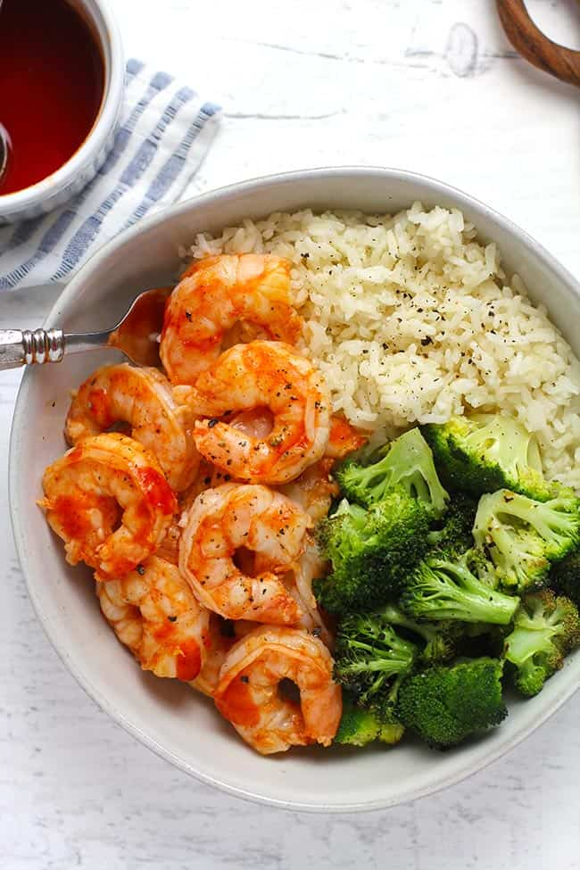 Overhead shot of a white bowl of honey sriracha shrimp, with rice and roasted broccoli, on a white background.