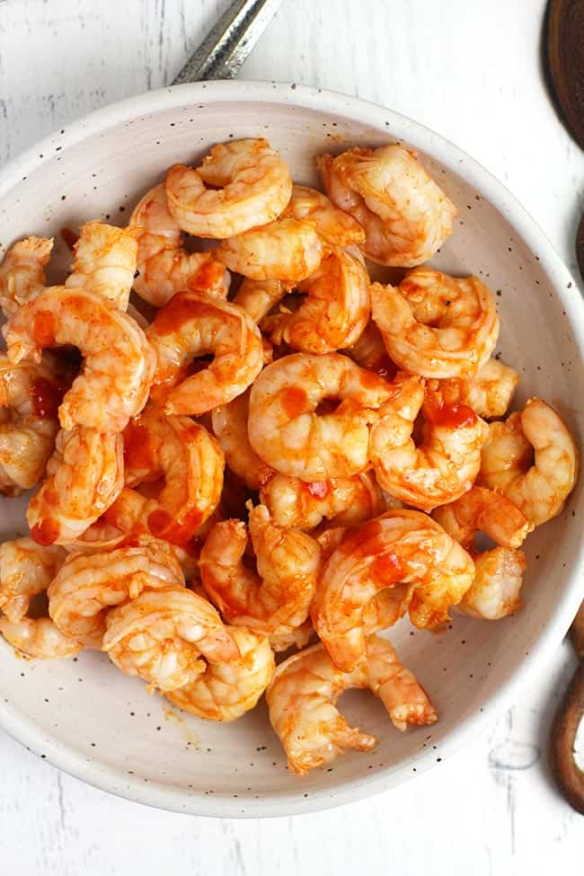 Overhead shot of a white bowl filled with cooked honey sriracha shrimp, on a white background.