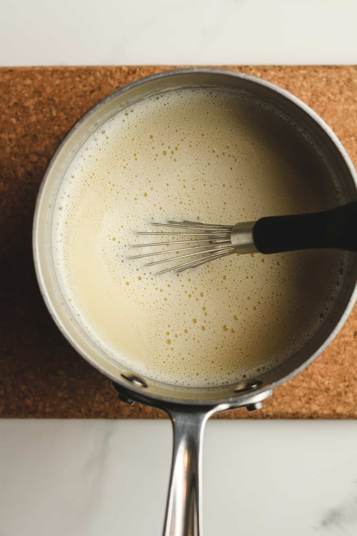 Overhead shot of a saucepan of the tempered egg mix.