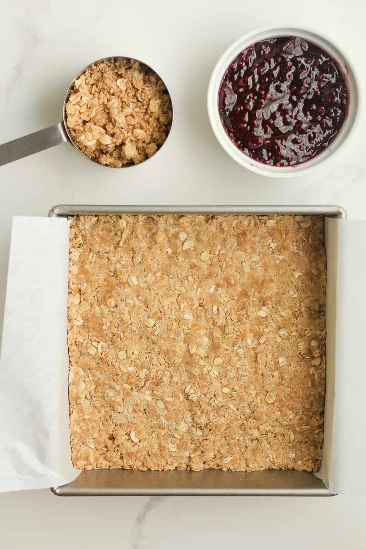 The crumble layer to the bars, with bowls of jam and the reserved crumble.