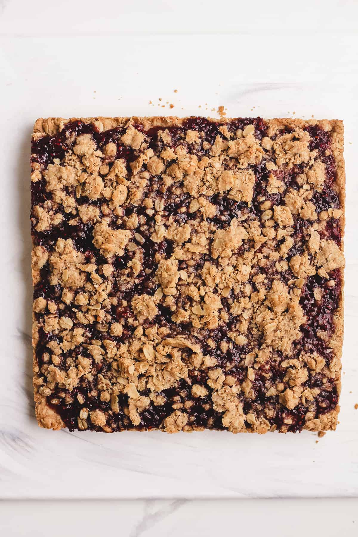 A just baked square of oatmeal raspberry jam bars.