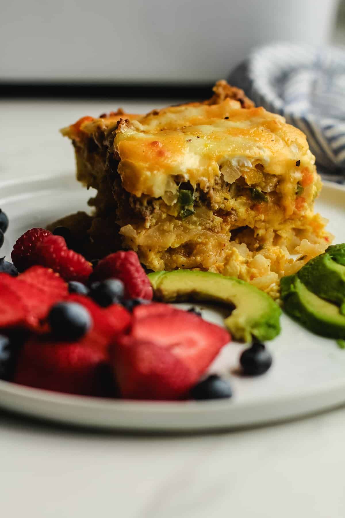 Side shot of a square of breakfast casserole on a plate with avocado and fruit.